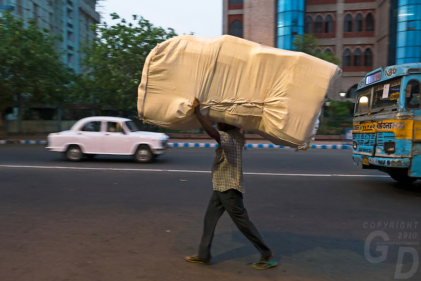 A porter carrying a heavy Load In the streets of Kolkata, West Bengal, India
