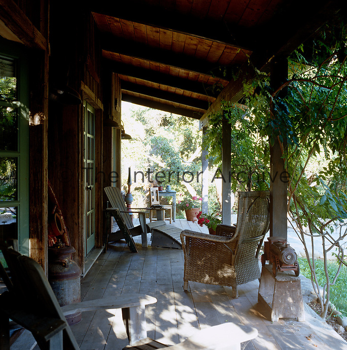 The porch to the guest house is furnished with painted sun loungers and has a view over the valley
