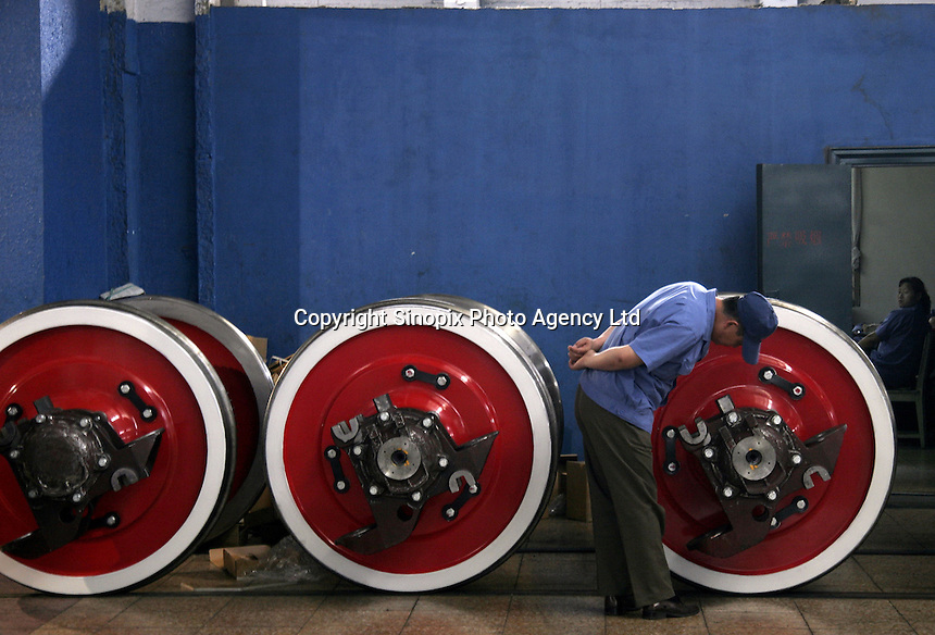 A Chinese worker inspects wheel bases of locomotives at the state-owned Datong Electric Locomotive Co. LTD in Datong, Shanxi Province, China. China's developing economy has created a huge demand for faster and more powerful locomotive engines to move its people and goods within its vast and expanding railway network, the Datong company is currently working together with several western partners including Alstom of France and ABC of the U.S..05 Jul 2005