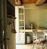A Provencal kitchen with tiled walls and an open door to the garden