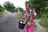INDONESIA, Flores, a woman and her baby stand on the side of the road in Dintor village