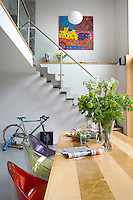 The open staircase leads from the dining area to the living space above where a framed abstract painting is a striking focal point on an adjacent wall