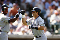 Tino Martinez of the New York Yankees is greeted by teammate Darryl Strawberry during a game against the Anaheim Angels circa 1999 at Angel Stadium in Anaheim, California. (Larry Goren/Four Seam Images)
