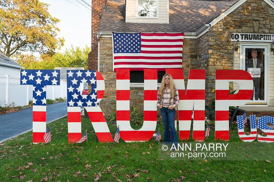 "Bellmore, New York, USA. November 2, 2016. EILEEN FUSCALDO, a Donald Trump Supporter, stands in front of TRUMP display, one of many in her Halloween front yard display for the Republican presidential candidate, D. J. Trump, and against Democratic one, H. R. Clinton.  On her front door is a life-size cardboard Trump holding ""The Silent Majority Stands with Trump"" sign."