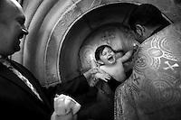 """Nagorny-Karabach, 14.05.2011, Shushi. Ein Junge wird von einem Proester in  der Ghazanchetsots Kathedrale getauft. """"The Twentieth Spring"""" - ein Portrait der s¸dkaukasischen Stadt Schuschi, 20 Jahre nach der Eroberung der Stadt durch armenische K?mpfer 1992 im B¸gerkrieg um die Unabh?ngigkeit Nagorny-Karabachs (1991-1994). A priest baptizes a young boy in Ghazanchetsots cathedral. """"The Twentieth Spring"""" - A portrait of Shushi, a south caucasian town 20 years after its """"Liberation"""" by armenian fighters during the civil war for independence of Nagorny-Karabakh (1991-1994). .Un prêtre baptise un jeune garçon dans la cathédrale de Ghazanchetsots. """"Le Vingtieme Anniversaire"""" - Un portrait de Chouchi, une ville du Caucase du Sud 20 ans après sa «libération» par les combattants arméniens pendant la guerre civile pour l'indépendance du Haut-Karabakh (1991-1994)..© Timo Vogt/Est&Ost, NO MODEL RELEASE !!"""