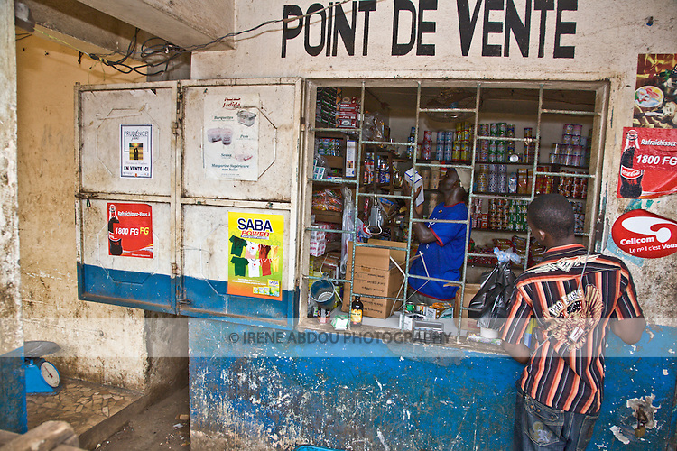 A wholesaler in Conakry, Guinea, stacks packages of Prudence Plus condoms on the shelves.  Prudence Plus is distributed by the international social marketing organization, Popualtion Services International.