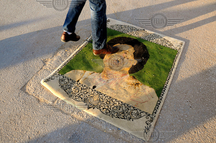 People walking over a portrait of Col Muammar Gadaffi in Benghazi, Libya's second city, now under the control of rebel forces. On 17 February 2011, an uprising against the 41 year rule of Col Muammar Gadaffi started in eastern Libya...