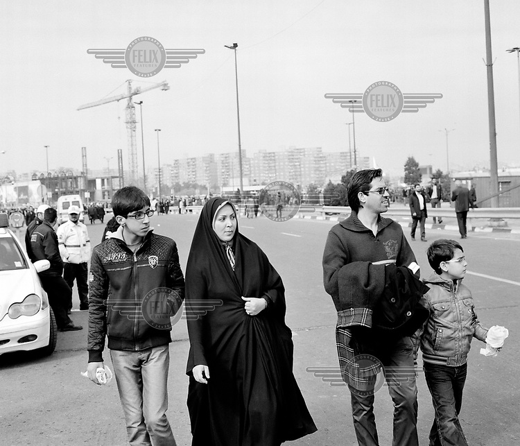 A family walking in central Tehran, enjoying some early Spring sunshine during a day of celebrations for the 35th anniversary of the Iranian Revolution.