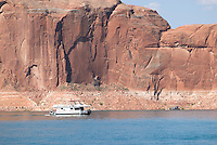 houseboat backed by sandstone cliffs on Lake Powell