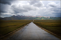 A rain-wet road leads to the Tibetan high mountains.