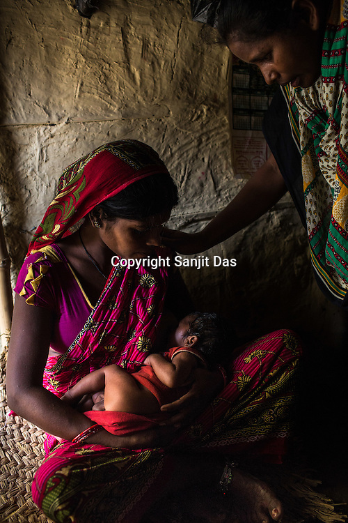 Srikanthi Devi feeds her son while the community nurse teaches her the right way to hold and breastfeed her son in Ramgarwa village in Raxaul district in Bihar, India.