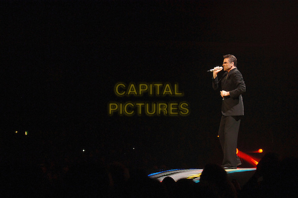GEORGE MICHAEL.Perfoming at Earl's Court, London, UK..half 25th , 2006 .full length stage concert live gig performance music profile sunglasses shades black suit singing.CAP/BEL.©Belcher/Capital Pictures