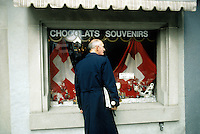 Switzerland. Zoug. Old town. The first of August is the national day of Switzerland. An old man looks at a shops window selling chocolate and souvenirs. Swiss flags and cow. Gift shop.  © 1989 Didier Ruef