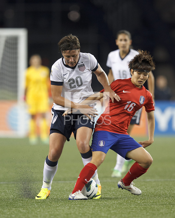 USWNT substitute forward Abby Wambach (20) tackles Korea Republic substitute forward Kim Sangeun (16). In an international friendly, the U.S. Women's National Team (USWNT) (white/blue) defeated Korea Republic (South Korea) (red/blue), 4-1, at Gillette Stadium on June 15, 2013.