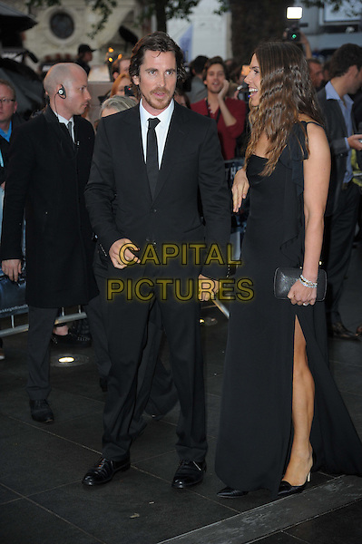 Christian Bale; Sibi Blazic.'The Dark Knight Rises' European premiere at Odeon Leicester Square cinema, London, England..18th July 2012.full length dress one shoulder married husband wife black suit white shirt tie beard facial hair profile side slit split .CAP/CAS.©Bob Cass/Capital Pictures.