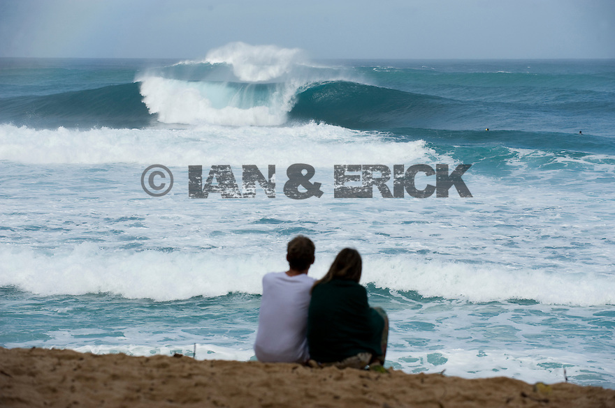 Couple looking at an empty wave at Pipeline on the Northshore of Oahu in Hawaii.