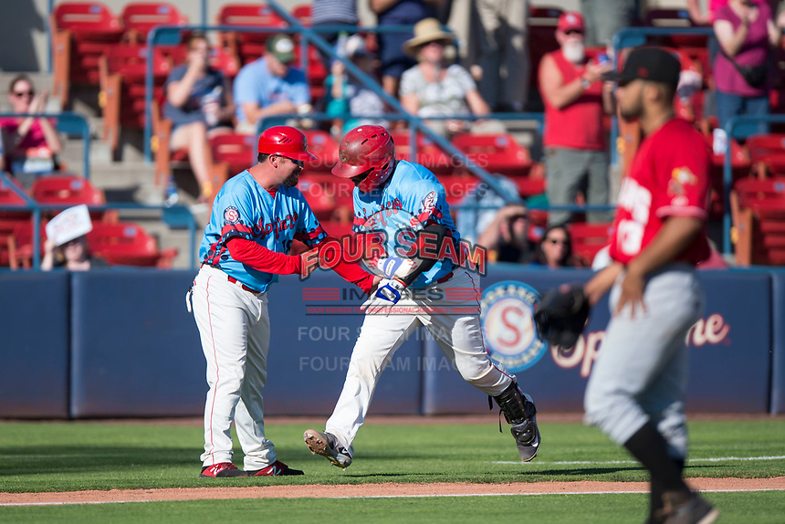 Spokane Indians catcher Isaias Quiroz (11) is congratulated by manager Kenny Holmberg after hitting a home run during a Northwest League game against the Vancouver Canadians at Avista Stadium on September 2, 2018 in Spokane, Washington. The Spokane Indians defeated the Vancouver Canadians by a score of 3-1. (Zachary Lucy/Four Seam Images)
