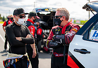 Jul 12, 2020; Clermont, Indiana, USA; NHRA funny car driver Jonnie Lindberg (left) talks with Tommy Johnson Jr during the E3 Spark Plugs Nationals at Lucas Oil Raceway. This is the first race back for NHRA since the start of the COVID-19 global pandemic. Mandatory Credit: Mark J. Rebilas-USA TODAY Sports