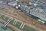Foto: VidiPhoto<br /> <br /> NIJMEGEN – Dankzij de lage waterstand van de Waal, kan er flink doorgewerkt worden aan de herinrichting van de Waalkade in Nijmegen. Op dit moment is de asfaltlaag verwijderd en worden kabels en leidingen verlegd. De kade wordt daarna gedeeltelijk verlaagd en krijgt een groene inrichting met gras en bomen. In de nieuwe situatie is dit deel van de Waalkade dan niet meer niet langer toegankelijk voor doorgaand autoverkeer. Wel komen er aan de beide zijden van het park keerlussen en (kort)parkeerplaatsen, zodat het mogelijk blijft om passagiers af te zetten. Het werk is naar verwachting half 2019 klaar. Doel is de Waalkade aantrekkelijker te maken voor toeristen. Zo komen er nieuwe terrassen en een groen evenemententerrein voor de Vierdaagsefeesten. Hoofdaannemer van het project is Dura Vermeer.
