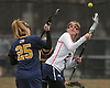 Olivia Dooley #21 of Manhasset, right, and Cara Scanio #25 of Massapequa battle for control of a faceoff during a Nassau County varsity girls lacrosse game at Manhasset High School on Tuesday, March 27, 2018. Manhasset won by a score of 11-8.