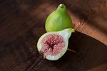 Organic, freshly picked ripe Kadota figs on a table, one fruit sliced in half showing purple pulp, artistic food still life on wood background Image © MaximImages, License at https://www.maximimages.com