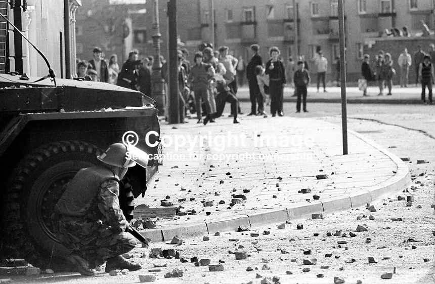 British soldier crouches behind an armoured personnel carrier during rioting and stone-throwing in the Bogside area of Londonderry, N Ireland, 9th July 1971. The rioting was prompted by the deaths of two local men, Seamus Cusack and Desmond Beattie, who were shot by soldiers in disputed circumstances. 197107090261a<br />
