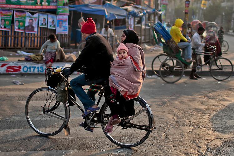 A Bangladeshi man rides a bicycle with his family early morning in Dhaka, Bangladesh.