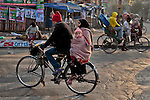 A Bangladeshi man rides a bicycle with his family early morning in Dhaka, Bangladesh.