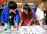 NWA Democrat-Gazette/DAVID GOTTSCHALK  Taiki Shibamoto (from left), of Yokohama, Japan, and a freshman at the University of Arkansas, helps Shilpi Mukherjee, a graduate student at the University, write in Japanese Calligraphy, as Kat Wislson, a senior at the University, waits for a turn Monday, November 16, 2015 in the Arkansas Union International Connections Lounge on the campus in Fayetteville. The students were participating in the International Student Organization Bazaar presented by the International Student Organization at the University of Arkansas on the first day of International Education Week. The bazaar featured displays, food and entertainment from 18 different countries and asked students to wear traditional attire from their country.
