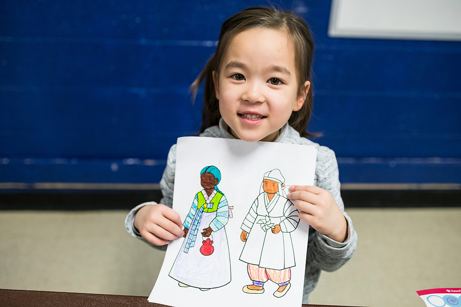 Eden Clausen shows off her colored drawing during a lunar new year event hosted by Families Through Korean Adoption (FTKA) in the gym and school cafeteria of St. Dennis Church in Madison, Wis., on Feb. 10, 2018. The event celebrated the passing of the lunar new year, and is one of several events for FTKA-member families and children to gather and enjoy cultural fun, food and play. (Photo by Jeff Miller - www.jeffmillerphotography.com)
