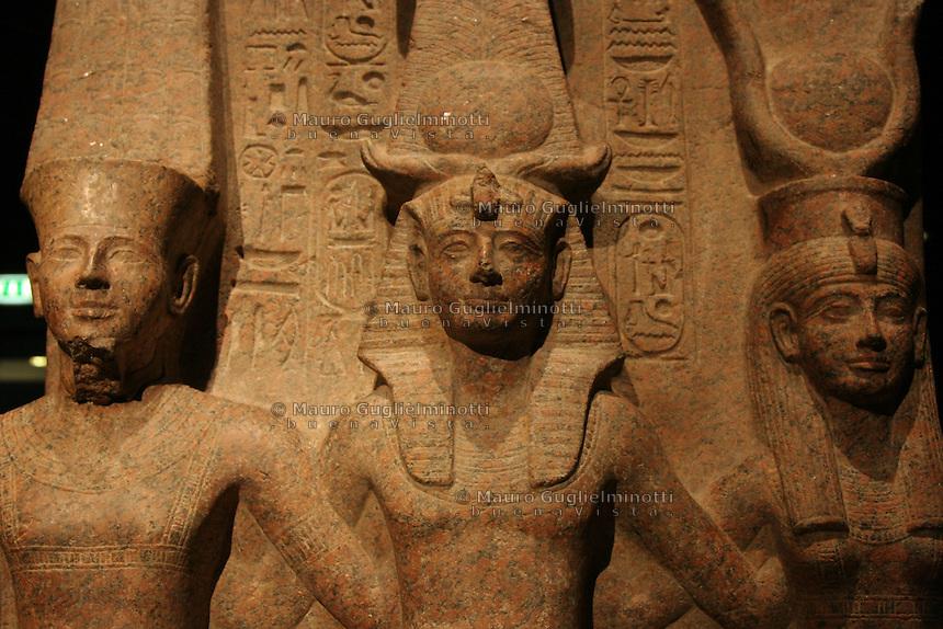 ITALIA - Torino - Museo Egizio  Il faraone Ramesse II con il dio Amon e la dea Mut; il faraone è seduto con il dio e la moglie, protettori e garanti della dinastia Il faraone indossa la corona atef composta dal disco solare tra corna dell'ariete sacro di Amon e dall'emblema della dea giustizia Maat....(granito rosa XIX dinastia regno di Ramesse II 1279-1213 ac tempio di Amon, Tebe)....red granyte XIX dynasty reign of Ramesses II 1279-1213 BC temple of Amon Thebes..the king is seated with the god Amon and his consort Mut both consdidered the protectors and guarantors of the New Kingdom royals.The king wears the atef-crown composed of the sundisk and Amun ram horns and teh Maat feathers of justice  particolare