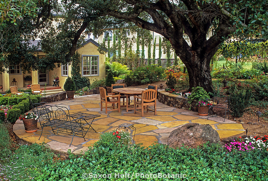 Cut stone rock masonry patio under oak in California backyard garden design by Nancy Driscoll