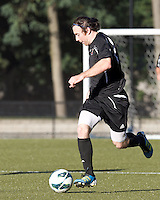Brown University midfielder Thomas McNamara (7) brings the ball forward. Brown University (black) defeated Boston College (white), 1-0, at Newton Campus Field, October 16, 2012.