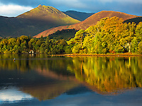 The sunrise breaks between some clouds and shines on the trees around Derwentwater near Keswick in the Lake District of England.