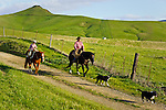 Father and son riding horseback at sunset, San Luis Obispo, California