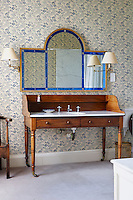 A contemporary triptych mirror hangs above a Victorian wood and marble washstand in the bathroom