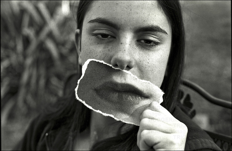 A young woman holding a photo of her mouth infront of her face