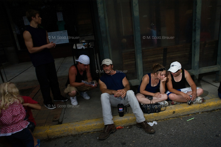 People sit on the sidewalk to watch activities at Evel Knievel Days in Butte, MT, USA.