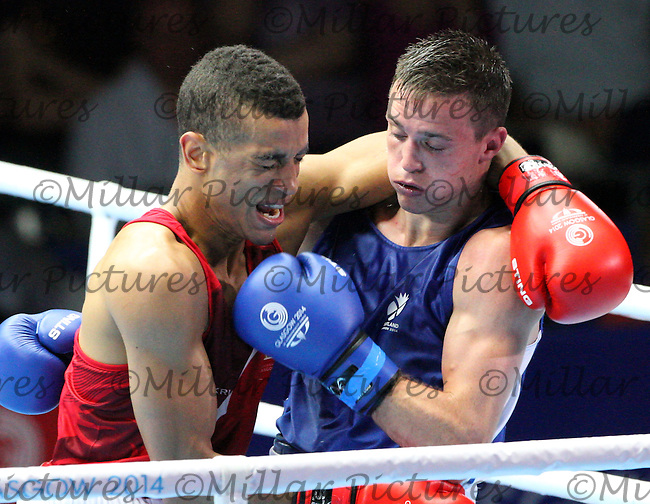 Samuel Maxwell of Team England in the red vest against Josh Taylor of Team Scotland in the Men's Light Welterweight Semi Final bout  in the Boxing for the 20th Commonwealth Games, Glasgow 2014 at the Scottish Exhibition and Conference Centre, Glasgow on 1.8.14.