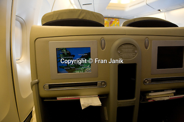 A shot of the interior of  the first class cabin on an Air France Aircraft. The graphic on the seatback screen shows the position of the Aircraft as it flys over the coast of France on a flight to Boston Massachusetts in the United States.