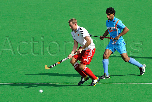 01.12.2012 Melbourne, Australia. Dan Shingles of England runs with the ball while SK Uthappa attempts to defend during the Men's Hockey Champions Trophy from the State Netball Hockey Centre.