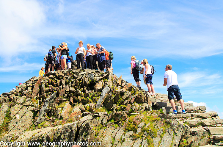 Walkers crowd onto the summit point, Mount Snowdon, Gwynedd, Snowdonia, north Wales, UK