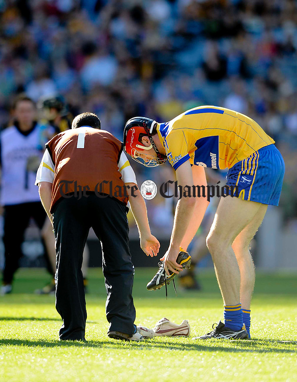 Clares Darach Honan changes his boots with help from Alan Dunne during their U-21 GAA All-Ireland final at Croke Park. Photograph by John Kelly.