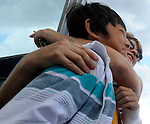 Brandi Gaulin, of Coventry, embraces Jay Song 12,  as Song arrives for his fourth summer, a two week stay, more than a dozen kids from the Fresh Air fund arrived  from New York City, Monday, July 28, 2014, at the former Golfland in Vernon. (Jim Michaud / Journal Inquirer)