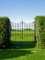 A simple paid of wrought-iron gates in a high hedge separate the garden from the surrounding fields