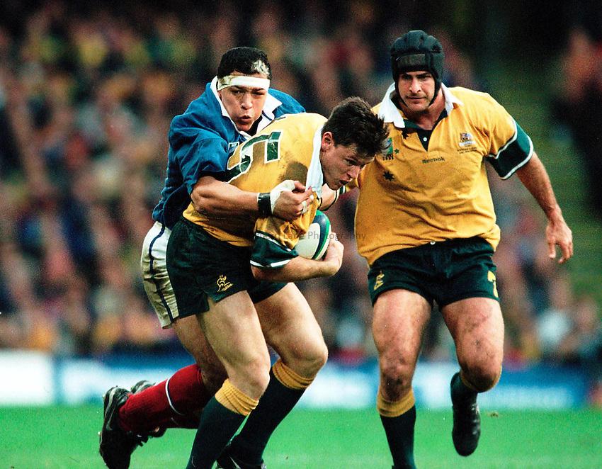 Photo. Richard Lane.Australia v France. 6/11/99..Matt Burke drives through the tackle of Abenazzi Benazzi.