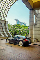 A Nissan 370Z Coupe GT sits in the porte-cochere of the Ritz-Carlton Millenia Singapore Hotel. In the background is the Marina Bay Sands hotel.