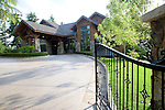 the gated entrance, circular entry, and covered entry drive, or porte cochere, of a large, lodge like, estate property in the late afteroon summer sunshine