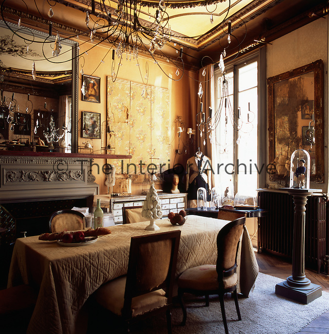 A gold dining room has a mirror set above an ornate fireplace and is furnished with an eclectic mix of furniture. Delicate metal chandeliers hang above a dining table and chairs in the centre of the room.