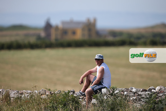 Spectator relaxing on the dry stone wall which abound the course during Round One of the 2014 Senior Open Championship presented by Rolex from Royal Porthcawl Golf Club, Porthcawl, Wales. Picture:  David Lloyd / www.golffile.ie